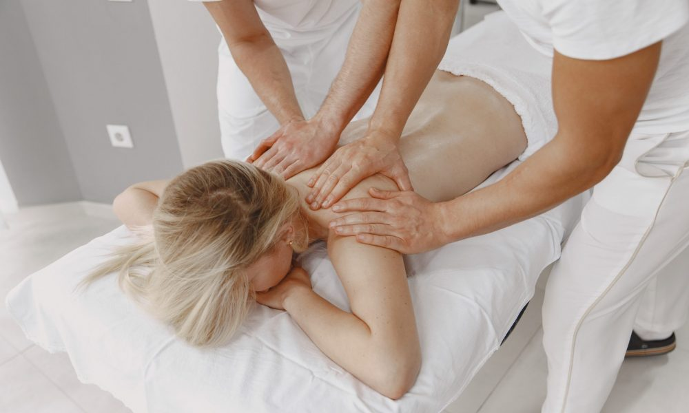 The massage with four hands. Concept of healthcare and female beauty. Two masseuses make a double  massage of a girl. Woman in a spa salon.