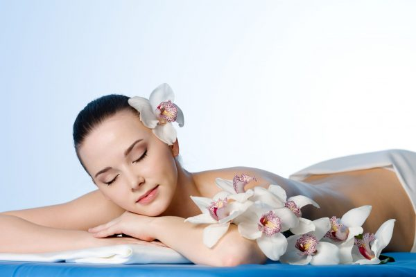Woman resting in beauty spa salon  with flowers - colored background